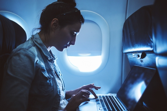 Young woman finishing her work in airplane