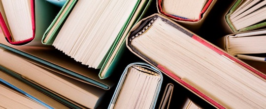 High angle view of many hardback books. Library or school.